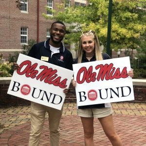 Marketing Assistants holding Ole Miss Bound yard signs