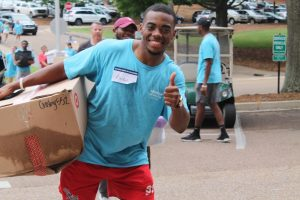 move in volunteer gives a thumbs up as he carries a box