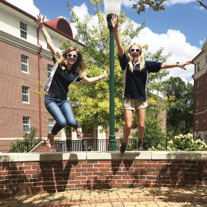 Marketing assistants jumping in courtyard
