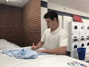 male student using a stain stick on a shirt